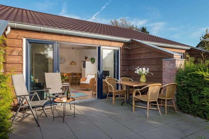 Het Reterink - In wat ooit een koeienstal was, zijn nu vijf luxe vakantiewoningen - Afgescheiden eigen terras met tafel, stoelen en zonnestoelen